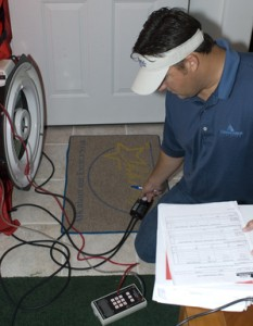 Photo of research knelt down adjusting controller of blower door for energy audit.
