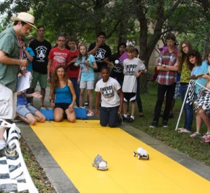 Students knelt down on yellow track watching model electric cars race side-by-side while crowd watches.