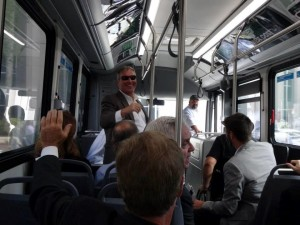 Photo of Mayor Dyer waving to passengers inside of electric bus.