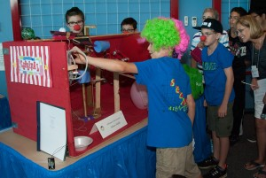 Students with red clown noses and neon colored wigs stand around contraption while judges look on.