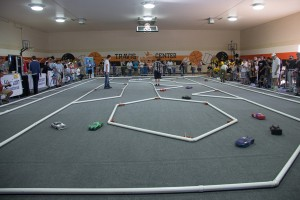 Remote controlled, model-sized hydrogen fuel cell cars race on carpeted track with PVC barriers.