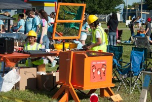 Girls in yellow hard hats and yellow construction vests prepare food to be cooked in their orange colored solar cooker.