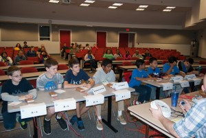 Students sitting at tables in double-elimination science bowl competition.