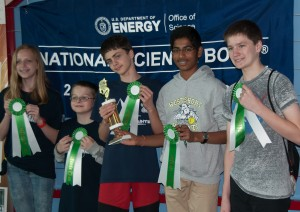 Students holding green and white ribbons in front of National Science Bowl backdrop.