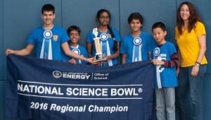 Winning students and teacher standing in front of banner, wearing ribbons and holding trophy.