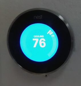 NEST thermostat reading 76 degrees installed on wall