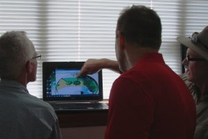 Two FSEC employees review solar access maps with business owner.