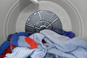 Clothes and towels inside the dryer, photo.