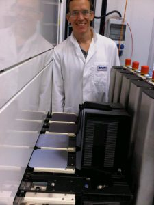 UCF researcher, Kris Davis, stands next to the ACPVD system that deposits metal oxide material onto silicon wafers.