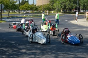 Six electric go-cart-style cars starting the race in a parking lot.