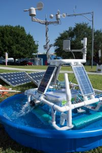 Solar panels arranged on a pyramid designed of PVC tubing that sits inside a child-sized swimming pool with water in it.