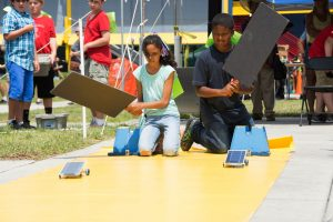 Female student and male student at the starting line of the Junior Solar Sprint yellow track, racing their model-size solar cars. Female student's car is slightly ahead of male's car.