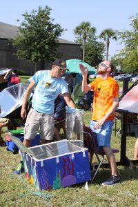 One male student positions the solar cooker while the other male student stands behind the cooker, stands behind the cooker, facing the sun and uses his hand to determine the path of the sun in relationship to the cooker.