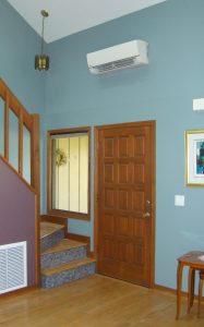 Interior of townhouse with staircase by front door. Return air grill under on side of staircase with mini-split ac unti above front door.