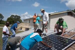 Adults students in the Installing Photovoltaic Systems course receive hands-on instruction and install PV panels on mock residential roof systems.