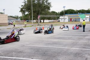 Nine electric go-carts racing at green flag