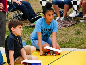 Female student from Saturn Elementary School and a male student prepare to race their Junior Solar Sprint cars, which were modified to run on batteries instead of solar due to the cloudy sky.