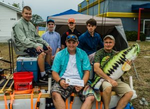 Five male students and instructor sits on their pontoon barge equipped with cooler, fishing poles and trolling motor.