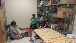 Three students sitting around contraption, which spanned from a long table and onto the floor.