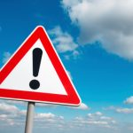 Warning sign, red outline triangle with black exclamation point in middle, cludy blue sky background