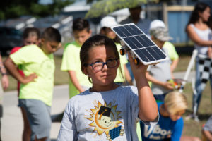 Student at EnergyWhiz event holding up Junior Solar Sprint model car in sun, partially shading face.